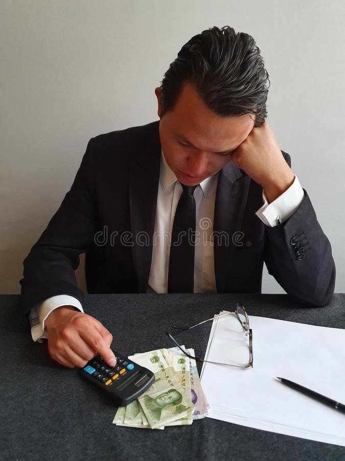 thoughtful young businessman analyzing budget and Chinese money on the table stock photos