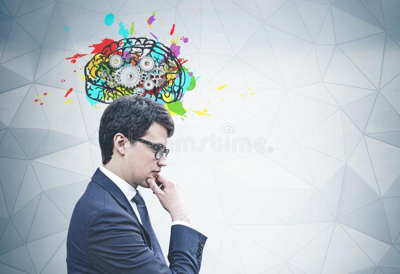 Thoughtful young businessman, cog brain royalty free stock photo