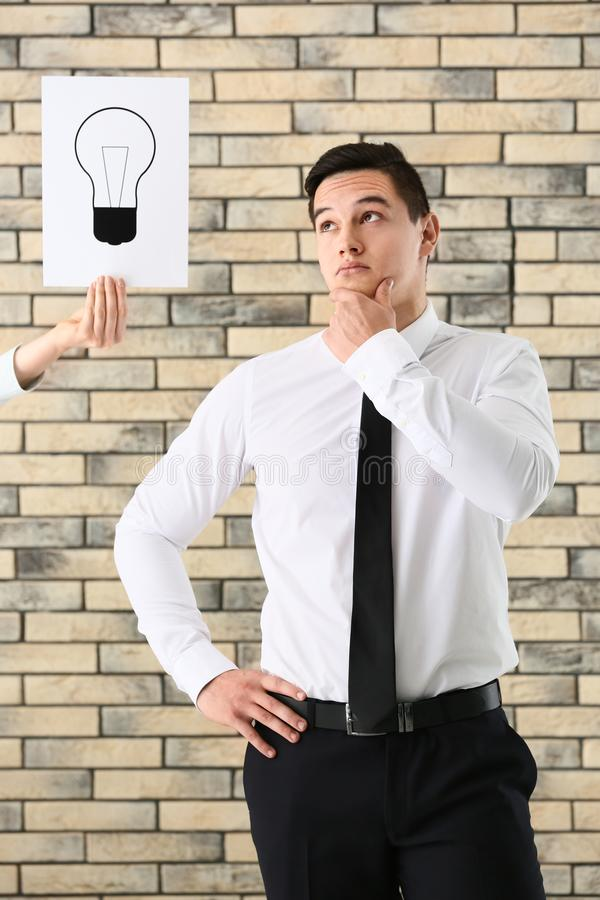 Thoughtful young businessman and female hand holding paper sheet with drawn light bulb as symbol of idea against brick wall royalty free stock image