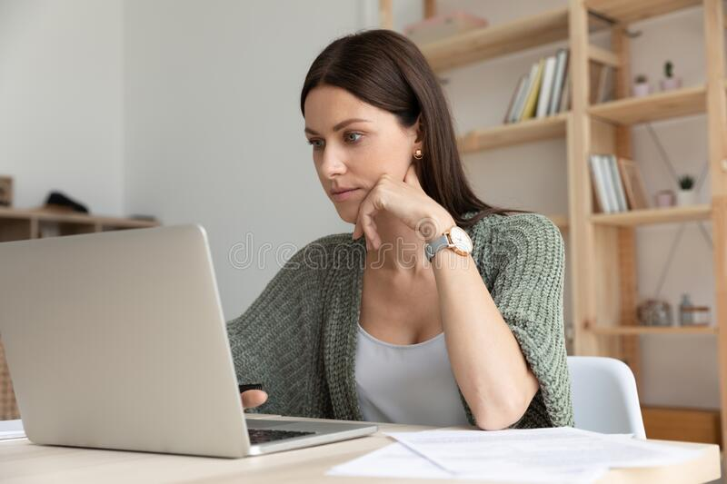 Thoughtful young businesswoman sitting at table with computer. stock image