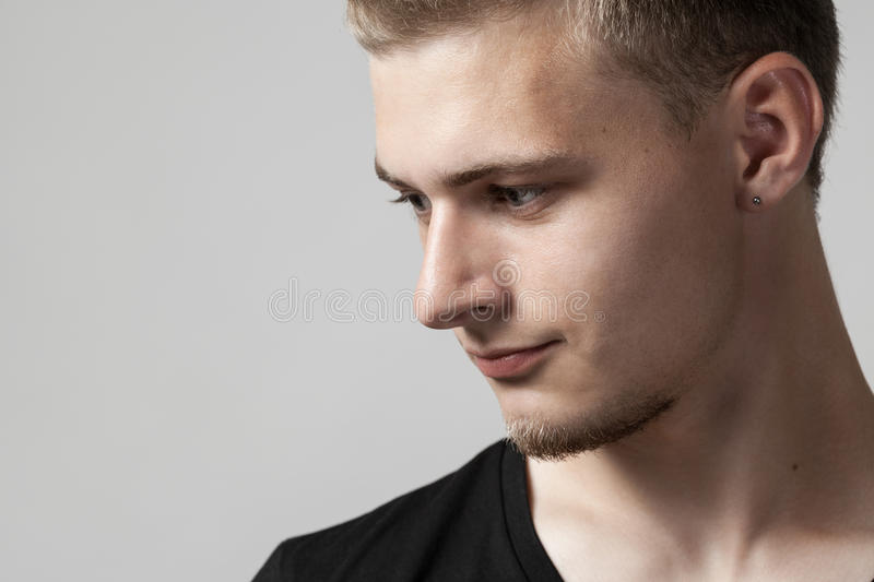 Thoughtful young caucasian man isolated on gray stock photos