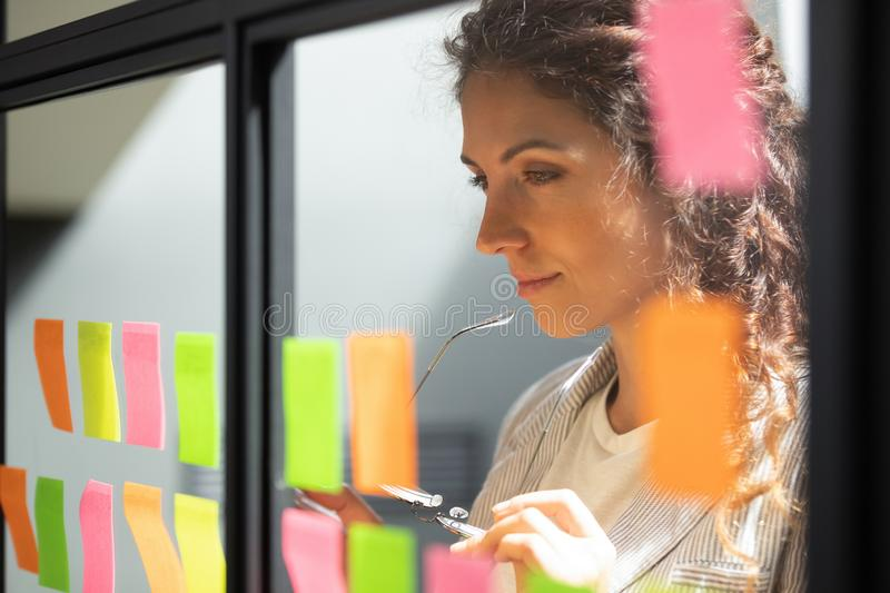 Thoughtful young female boss team leader looking at kanban board. stock photography