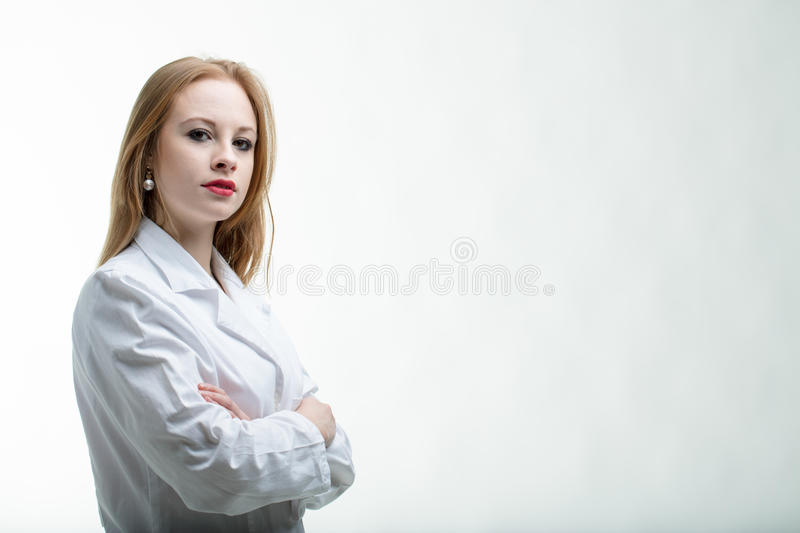 Thoughtful young female doctor with folded arms stock photography