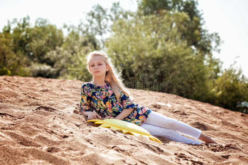 Thoughtful young girl resting on beach stock photos