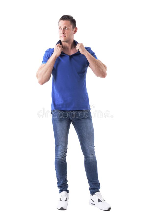 Thoughtful young handsome man fashion model holding polo shirt collar looking up. royalty free stock photo