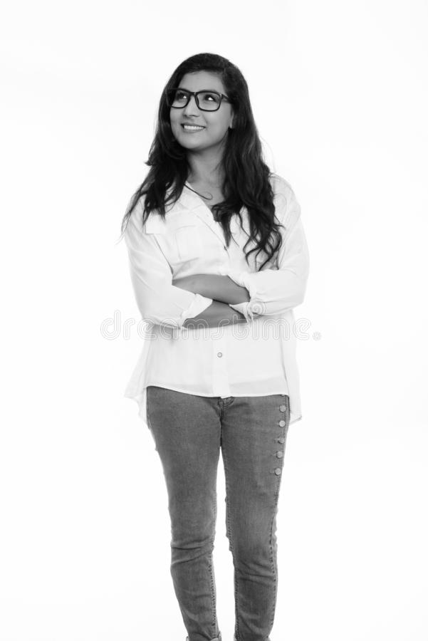 Thoughtful young happy Persian woman smiling and standing with arms crossed royalty free stock image