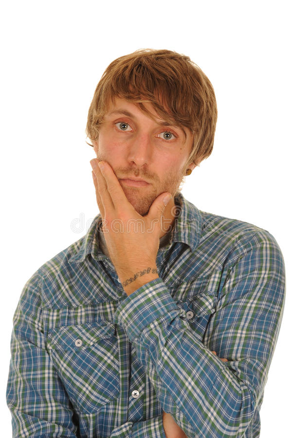 Thoughtful young man. In check shirt rubbing face with hand stock image