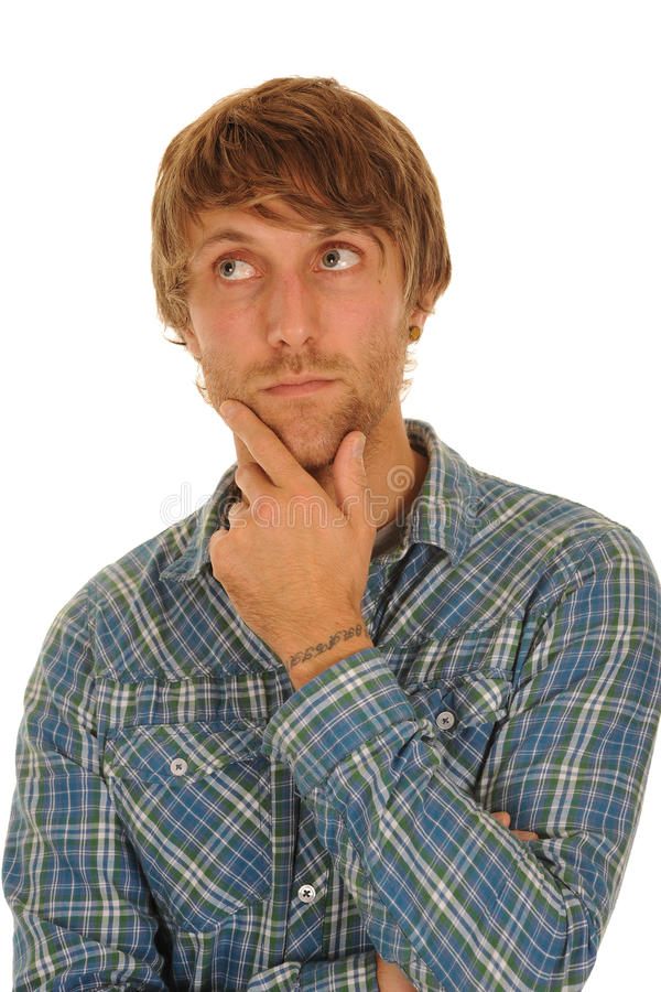 Thoughtful young man. In blue check shirt rubbing chin; isolated on white background royalty free stock photography