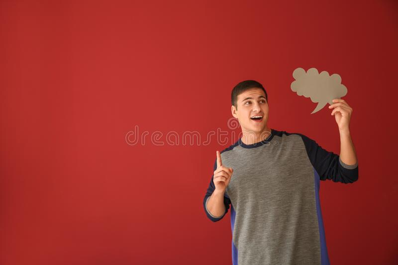 Thoughtful young man with speech bubble on color background stock images