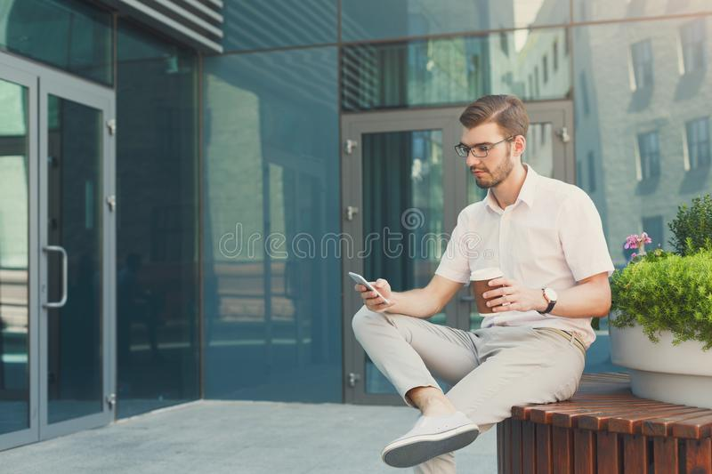 Pensive businessman with phone relaxing outdoors royalty free stock photo