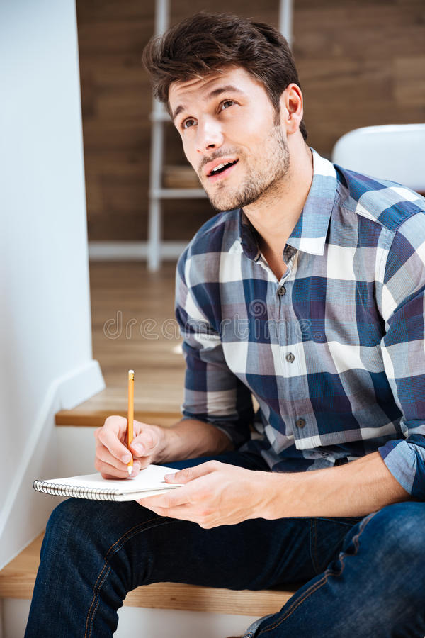 Free Thoughtful Young Man Thinking And Writing In Notepad At Home Stock Images - 76129004