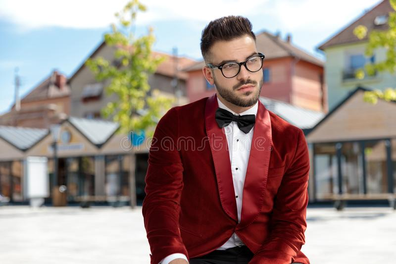 Thoughtful young man wearing red velvet tuxedo and thinking royalty free stock photos