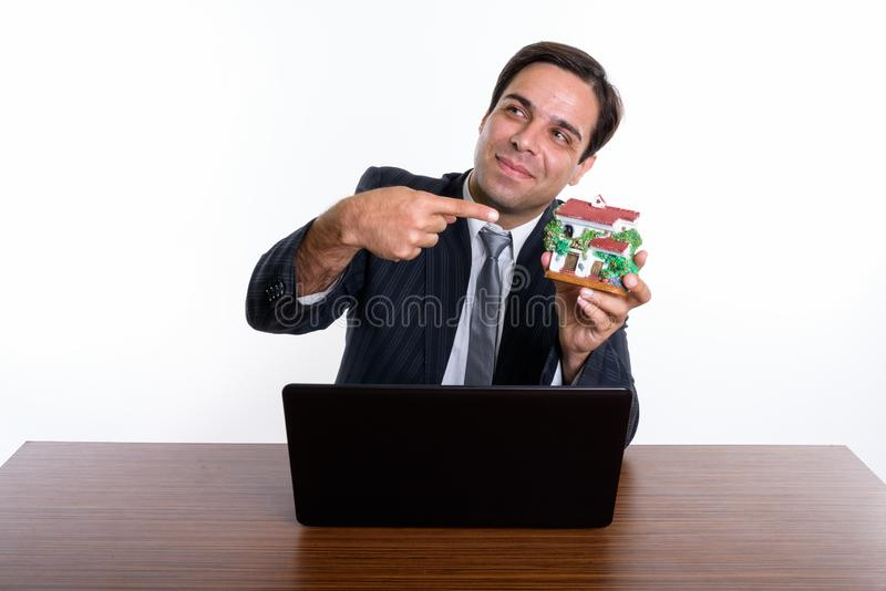 Thoughtful young Persian businessman holding and pointing at hou stock photos