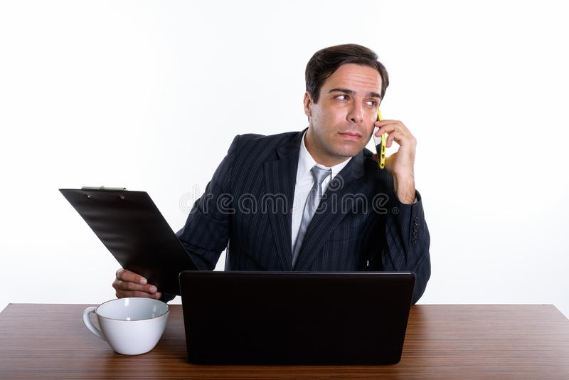 Thoughtful young Persian businessman talking on mobile phone whi royalty free stock photography