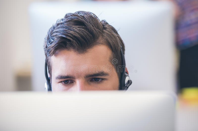 Thoughtful young programmer coding on computer stock photo