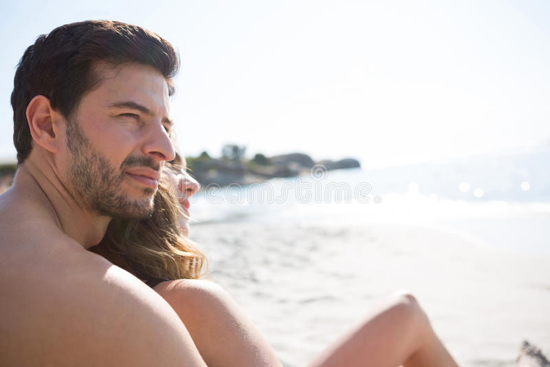 Thoughtful young shirtless man with his girlfriend sitting at beach stock photos