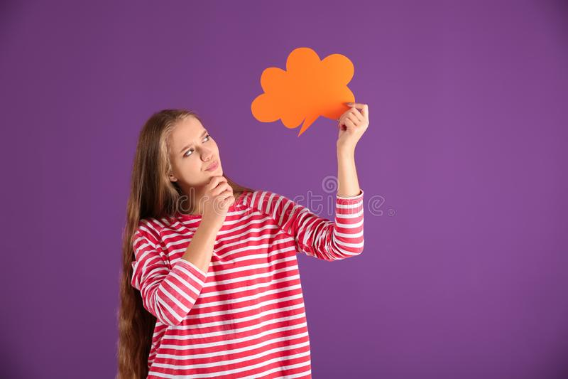 Thoughtful young woman with blank speech bubble on color background royalty free stock photography