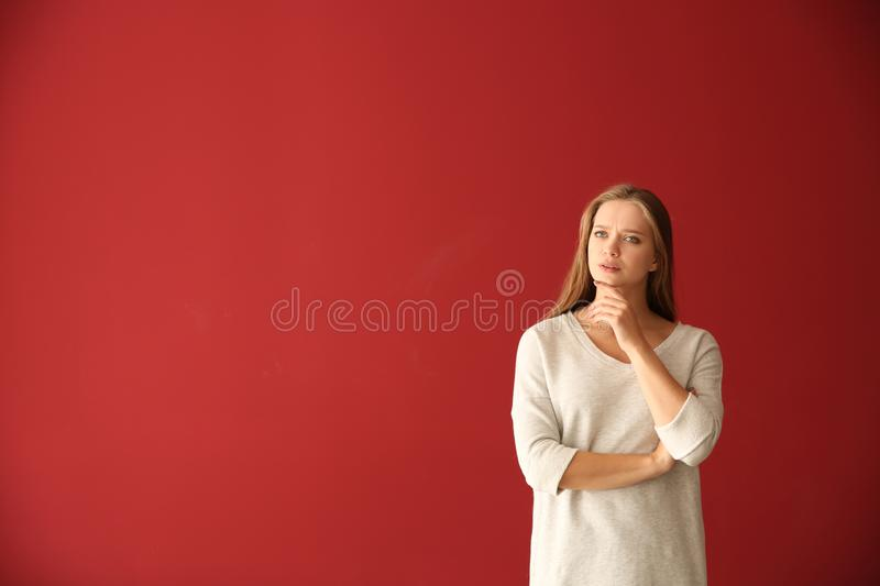 Thoughtful young woman on color background royalty free stock image