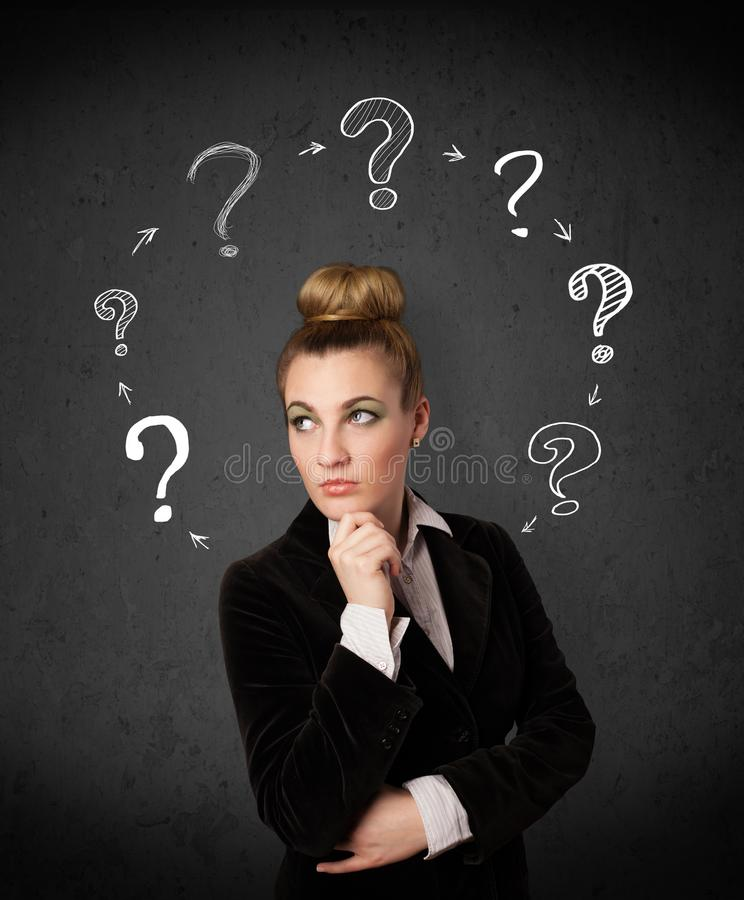 Young woman thinking with question mark circulation around her h. Thoughtful young woman with drawn question marks circulating around her head royalty free stock image