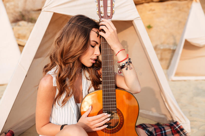 Thoughtful young woman with guitar in teepee on the beach. Portrait of attractive thoughtful young woman with guitar in teepee on the beach royalty free stock images
