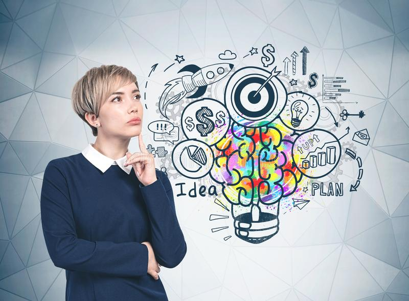 Thoughtful young woman and her business idea. Pensive blonde young woman in blue dress standing near gray wall with colorful business idea sketch drawn on it stock photos
