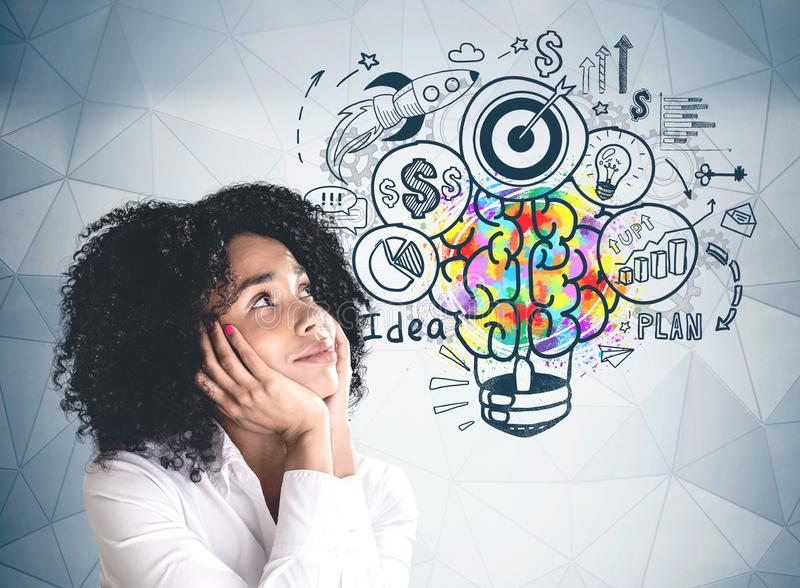 Thoughtful young woman and her business idea. Smiling young African American woman in white shirt looking at colorful business idea sketch drawn on gray wall stock photography