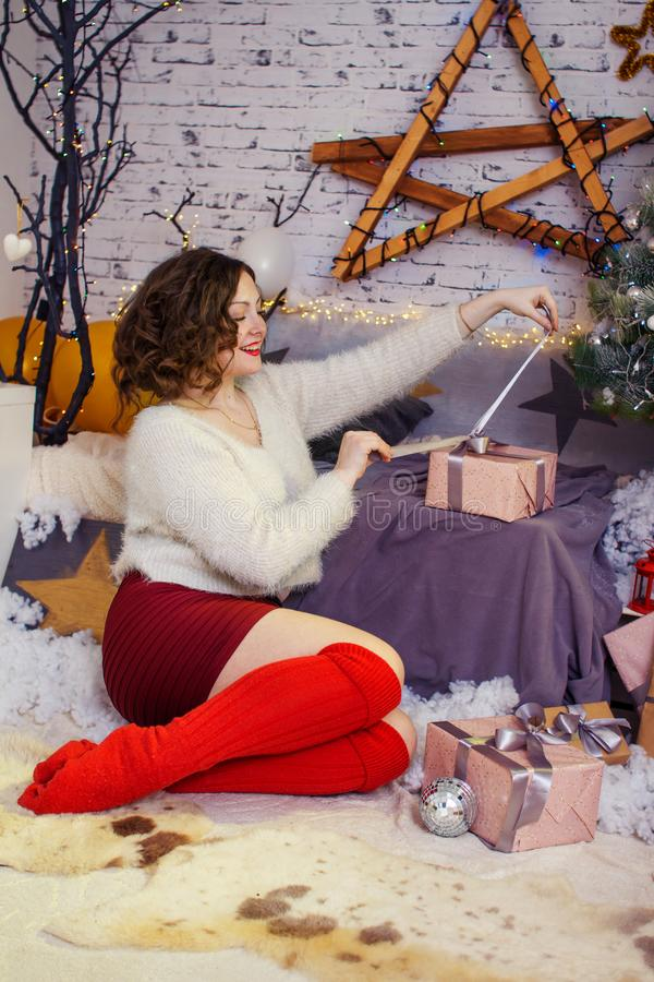 Thoughtful young woman with present box near christmas tree stock photo
