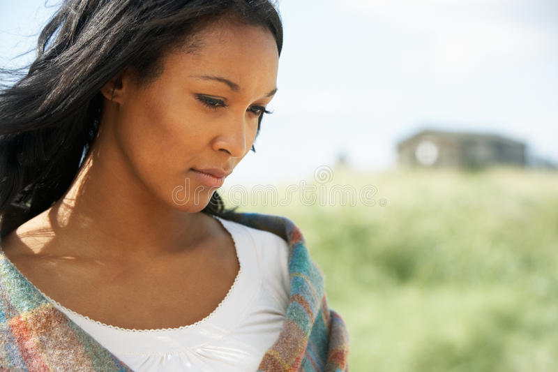Thoughtful Young Woman Standing On Beach royalty free stock photography