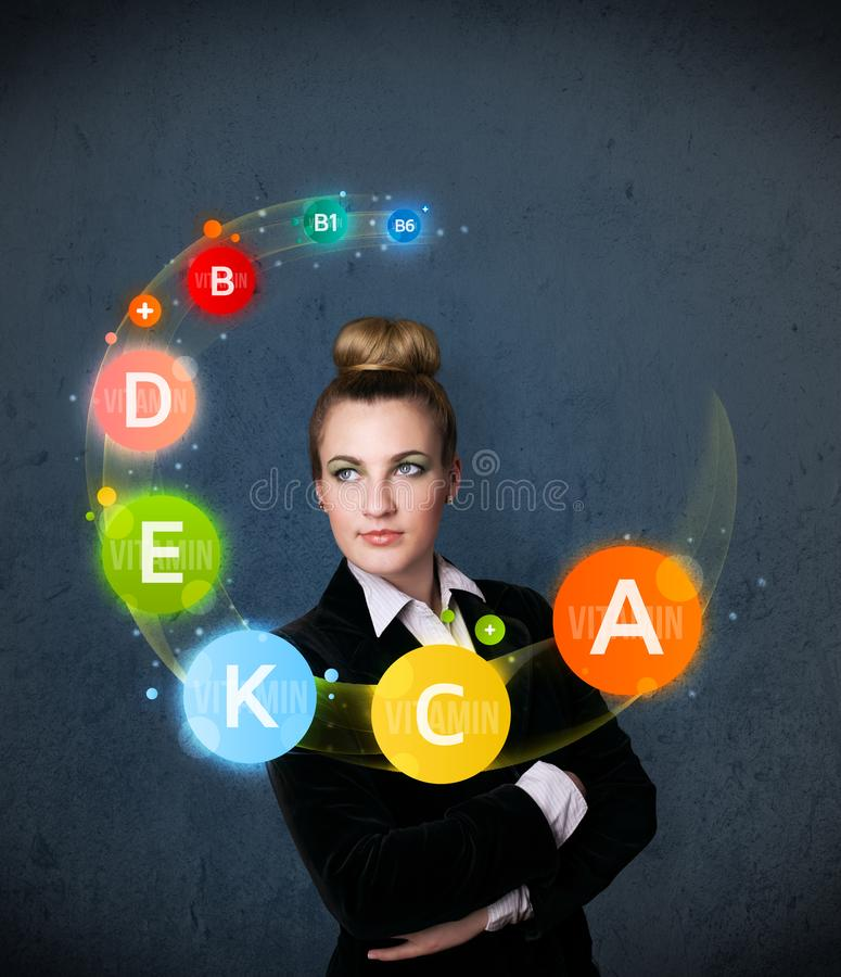 Young woman thinking with vitamins circulation around her head. Thoughtful young woman with vitamin icons circulating around her head royalty free stock image