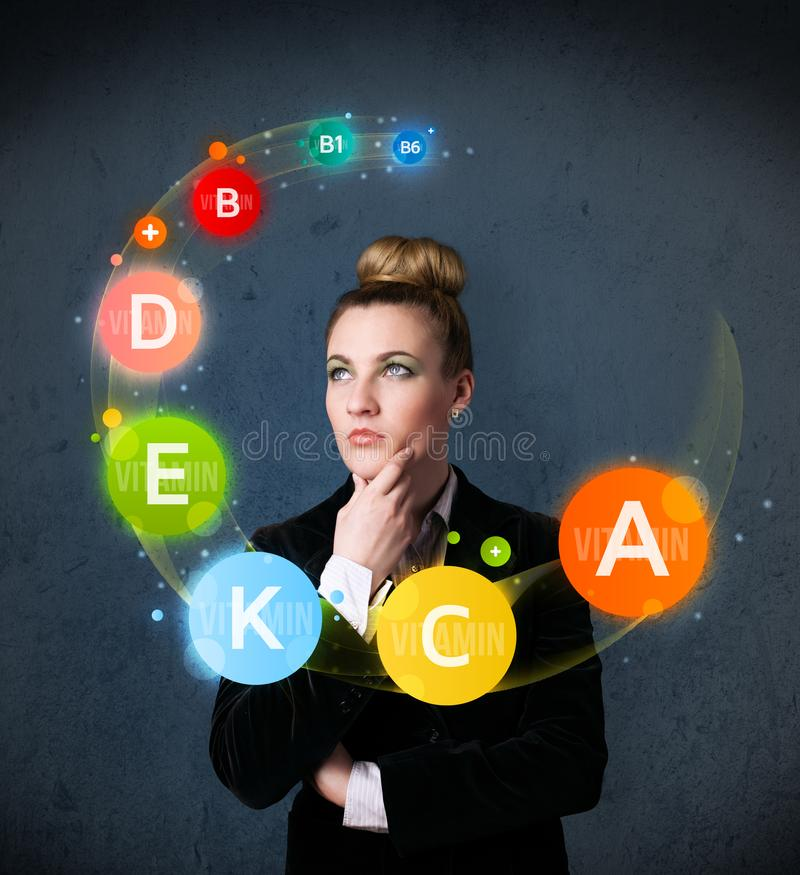 Young woman thinking with vitamins circulation around her head. Thoughtful young woman with vitamin icons circulating around her head royalty free stock photos