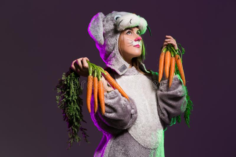 ThoughtfulEaster-Häschenmädchen mit Karotten stockbilder