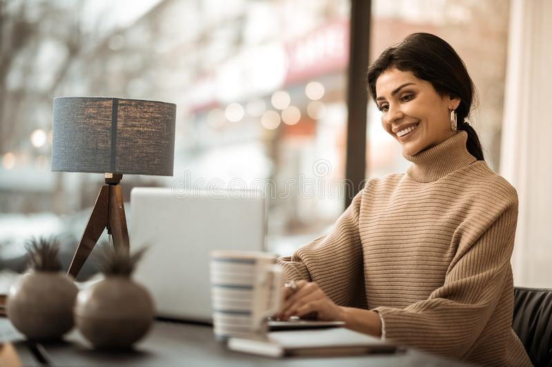 Busy concentrated good-looking woman in beige sweater royalty free stock photo
