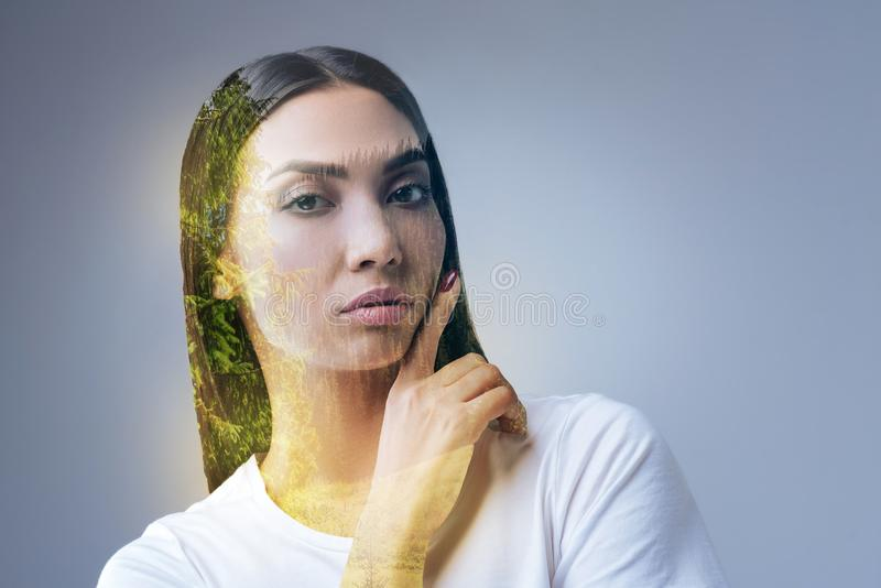 Pleasant positive woman inspiring with nature. Thoughts birth. Appealing young reflective woman staring at the camera and touching her face and has solution royalty free stock photo