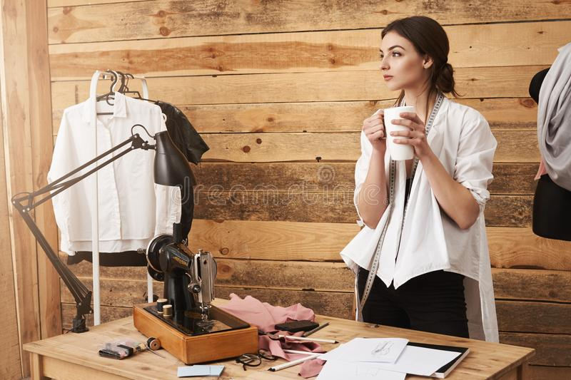 Thoughts carry me away. Young cute clothes designer standing in workshop, having break from sewing, drinking coffee and royalty free stock images