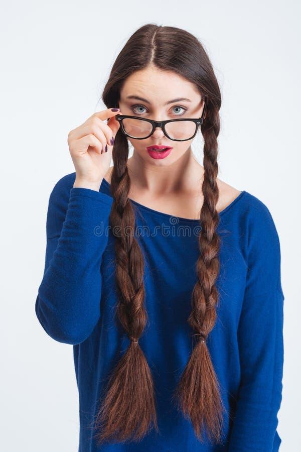 Thoughtulvrouw die met twee lange vlechten over glazen kijken stock afbeeldingen
