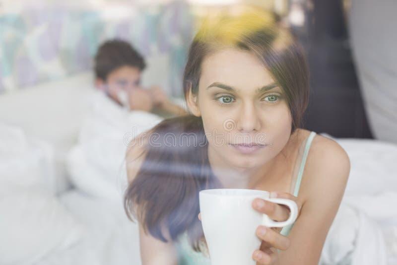 Thougtful kvinna som har kaffe hemma med mannen som ligger i bakgrund royaltyfri bild