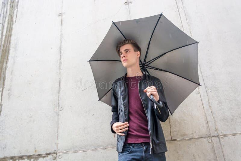 Thougtful Mann jungen jugendlich, der im Regen in der Stadt mit Regenschirm steht stockfoto