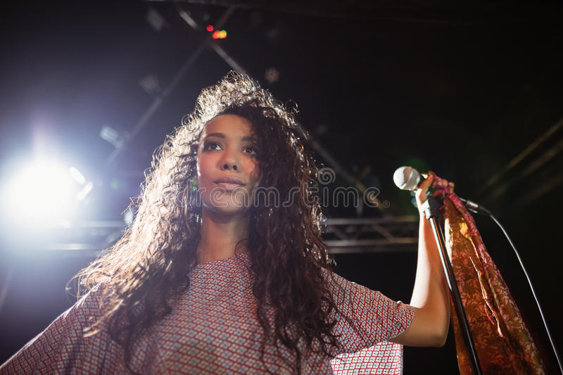 Thougthful young female singer holding mic at nightclub royalty free stock photos