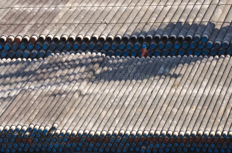 Thousands of pipes on the barge and man stock photography