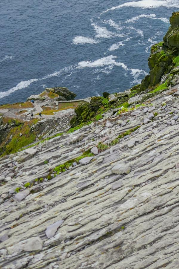 Wild Atlantic Way Ireland: Stunning view -- climbers return to sea level from Skellig Michael`s ancient unprotected staircasese stock photos
