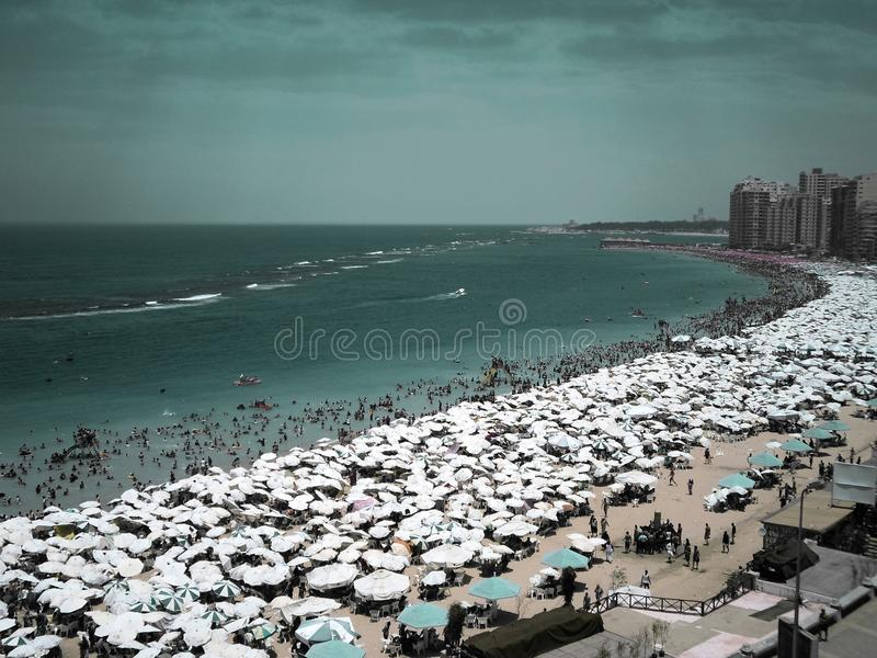 Thousands of umbrellas and people on the beach in Alexandria, Egypt stock photos