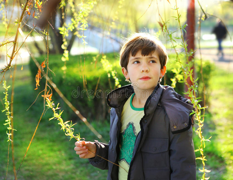 Thoutful portrait of preteen handsome boy on the spring park background stock photo