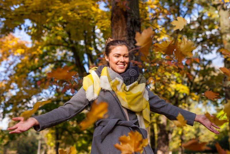 Thowing Bündel des schönen Mädchens colrful Blätter Autumn Time lizenzfreies stockbild