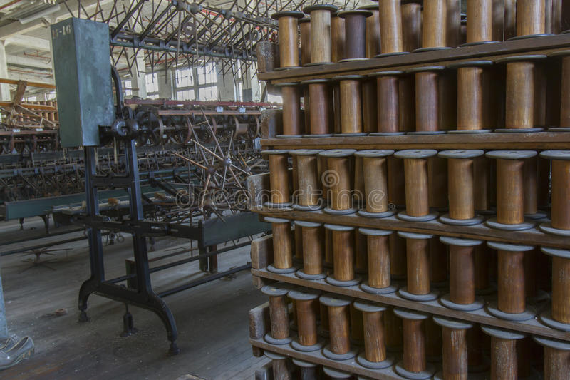 Thread factory floor with wooden bobbins. Rack of wooden bobbins with antique equipment on floor of turn of the century silk throwing factory stock photo