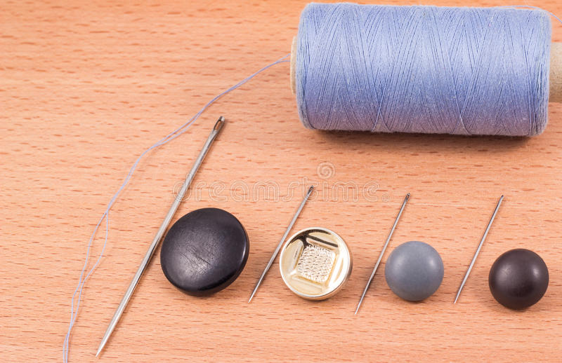 Thread a needle and buttons. Accessories for the textile industry with a needle and thread to sew buttons royalty free stock photo