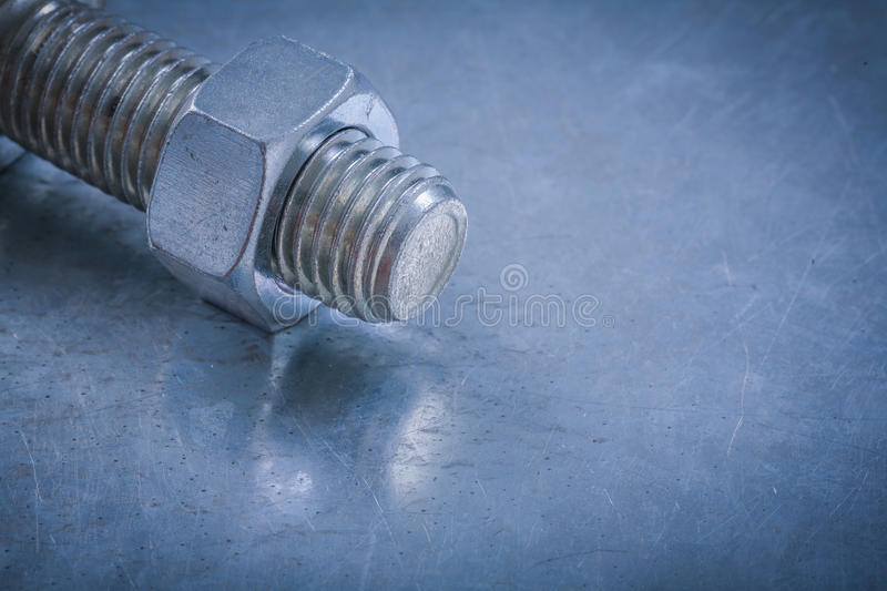 Threaded bolt detail and nut on metallic background construction. Concept royalty free stock images