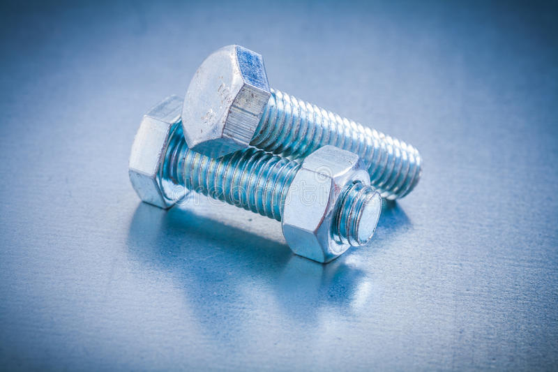 Threaded bolts with nut on metallic. Background construction concept royalty free stock photography