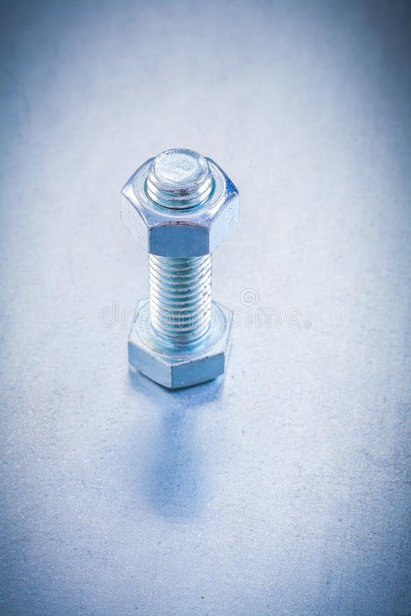 Threaded bolt with construction nut on. Metallic background repairing concept royalty free stock photos
