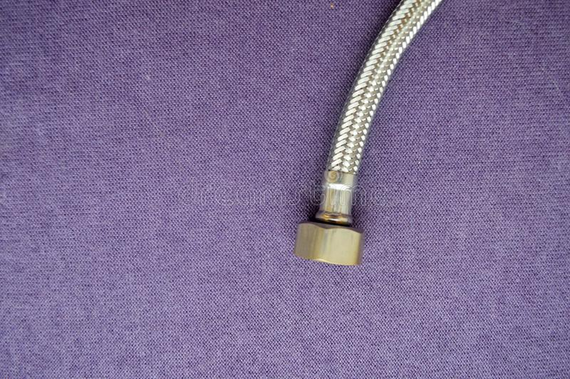 Threaded tap, reinforced, silver hose on a purple background. Plumbing fixture. A nut on the hose for a faucet royalty free stock photography