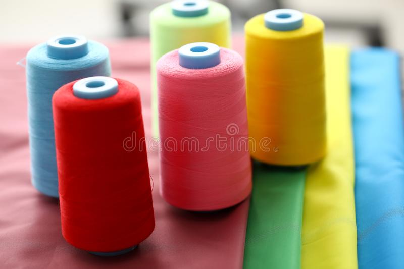 Threads for sewing on coils. Focus on multicolored spools of strings on fabric swatches. Bobbins in red, blue, pink, yellow and green colors. Fashioner market stock photo